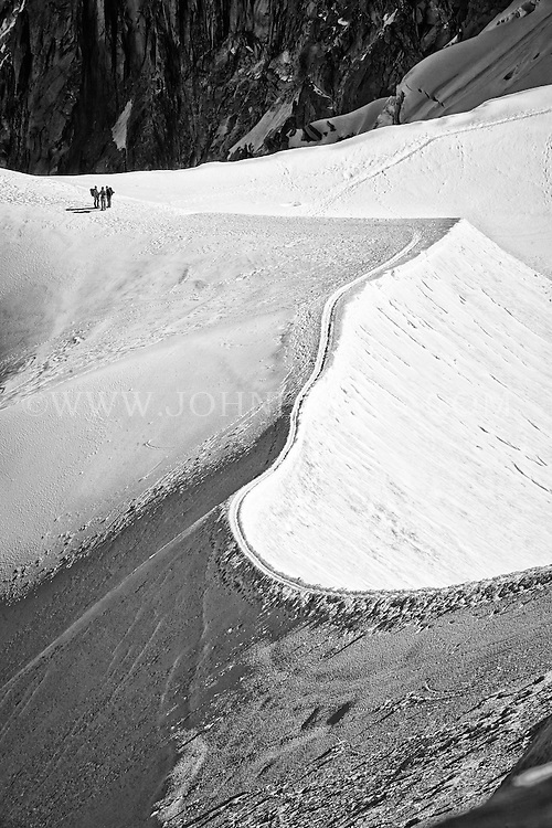 Black and white view of a trio of hikers walking across the French Alps - Chamonix, France.