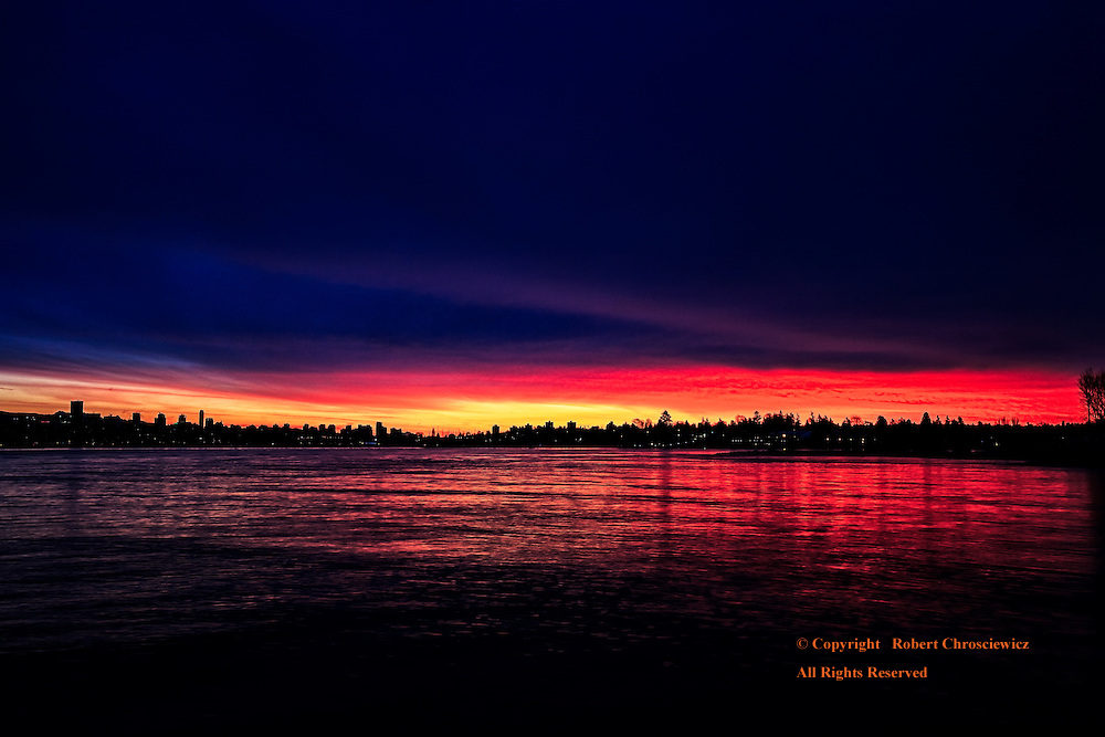 Vancouver Silhouette: Ocean-side at sunrise and Vancouver is silhouetted against a fiery gold and red sky, Vancouver British Columbia, Canada.