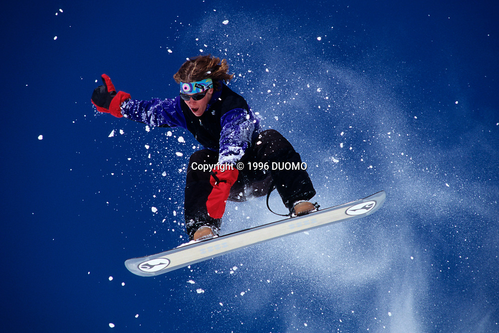 Young male snowboarder in action