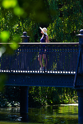 A woman wears a wide brimmed hat in Regents Park, London, as the heatwave continues to grip the capital. London, June 29 2018.