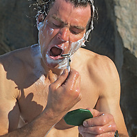 The late mountaineer Alex Lowe washes & shaves in an expedition base camp on Canada's Baffin Island