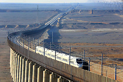 """File photo taken on Nov. 15, 2014 shows a bullet train running on the Lanzhou-Xinjiang high-speed railway, northwest China. """"Building more high-speed railways"""" has been a hot topic at the annual sessions of China's provincial legislatures and political advisory bodies intensively held in January. China has the world's largest high-speed rail network, with the total operating length reaching 19,000 km by the end of 2015, about 60 percent of the world's total. The expanding high-speed rail network is offering unprecedented convenience and comfort to travelers, and boosting local development as well. Chinese companies have developed world-leading capabilities in building high-speed railways in extreme natural conditions. High-speed railway routes across China have been designed to suit its varying climate and geographical conditions. The Harbin-Dalian high-speed railway travels through areas where the temperature drops to as low as 40 degree Celsius below zero in winter, the Lanzhou-Xinjiang railway passes through the savage Gobi Desert and the Hainan Island railway can withstand a battering from typhoons. The China Railway Corp. plans to spend another 800 billion yuan (around 120 billion U.S. dollars) in 2016, especially in less-developed central and western regions. EXPA Pictures © 2016, PhotoCredit: EXPA/ Photoshot/ Xinhua<br /><br />*****ATTENTION - for AUT, SLO, CRO, SRB, BIH, MAZ only*****"""