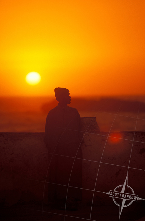 Moroccan man by the sea wall in Essaouira to watch the sunset.