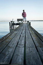Mature man standing on wooden jetty and looking at distance, Bavaria, Germany,