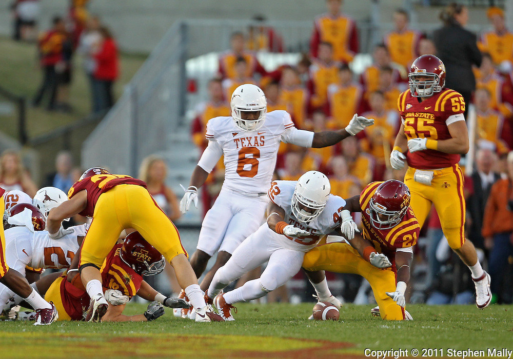 October 01, 2011: Texas Longhorns linebacker Tevin Jackson (42)jumps on a fumble as Iowa State Cyclones running back Shontrelle Johnson (21) battles for it during the first half of the game between the Iowa State Cyclones and the Texas Longhorns at Jack Trice Stadium in Ames, Iowa on Saturday, October 1, 2011. Texas defeated Iowa State 37-14.