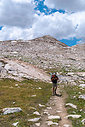 A teenage backpacker slogs along the John Muir Trail below Wanda Lake. John Muir Trail/Pacific Crest Trail; Sequoia Kings Canyon Wilderness; Kings Canyon National Park; Sierra Nevada Mountains, California, USA.