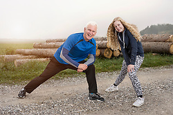 Father with his daughter stretching legs on footpath and smiling during dawn, Bavaria, Germany
