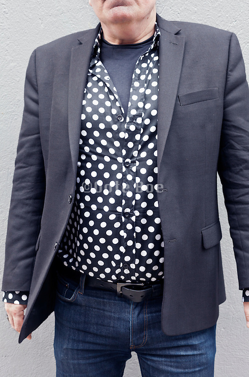close up of man wearing a black white dotted shirt