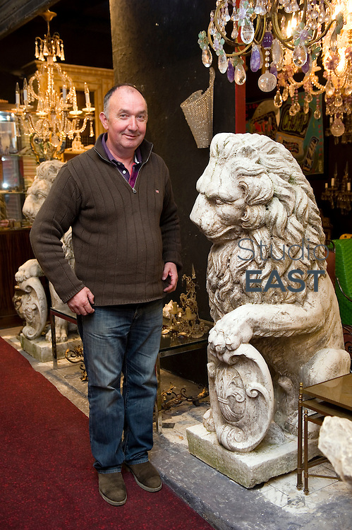 PARIS, FRANCE - APRIL 25: Antique dealer François Bachelier poses for a photograph by an antique lion as he 'tamed the lion' that is Grosvenor, in Saint-Ouen flea market, on April 25, 2014, outside Paris, France. Gerald Cavendish Grosvenor, the sixth Duke of Westminster and Britain's eighth richest man, has just bailed out of a nine-year battle against French dealers from two of the most prestigious antiques sections of the 130-year-old Paris flea market, or 'Marché aux puces de Saint Ouen' – the world's largest, with five million visitors a year. In 2005, the Duke paid €50 million (£41 million) for its high-end Serpette and Paul-Bert sections; last week he sold the lot at a reported €20 million loss to French landowner Jean-Cyrille Boutmy. (Photo by Lucas Schifres/Getty Images)