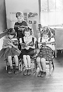 """0003-026. Children reading """"David's Friends at School"""" book during reading class in Evaline Elementary school, near Winlock, Washington. The photographer, Stuart Fresk, was a teacher there from 1935 to 1946."""