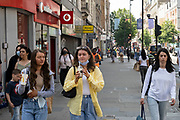 Two yourng women enjoy McDonalds drinks as the national coronavirus lockdown three eases towards the planned Freedom Day in just over two weeks, and people, many of whom are still wearing face masks while out on the street, come to Oxford Street shopping district on 22nd July 2021 in London, United Kingdom. Now that the roadmap for coming out of the national lockdown and easing of restrictions is set, dome medical professionals are suggesting thatsome safety measures are kept in place because of the increase in the Delta variant.