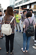 A group of young Koreans in Leicester Square pray and gently spread their faith in Christ and Christianity in London, United Kingdom. Carrying a wooden cross to mark the life of Jesus, they gather in prayer as a very public display of their religion and religious belief.