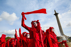 © Licensed to London News Pictures. 09/10/2019. London, UK. The Red Brigade of The Invisible Circus dressed in red with white makeup waves a red scarf under Nelson's Column on day three of the two weeks protest in Westminster. The activists are calling for the government to act on climate change. Photo credit: Dinendra Haria/LNP