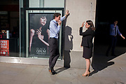 A man and woman chat in the street using hand gestures, a theme echoed in an Yves Saint Laurent fragrance ad. They are in the heart of capital's financial district (founded by the Romans in the 1st Century) and are outside their offices at lunchtime for a discussion on the street. Shadows of the man's head and hand that rubs his chin is also on the wall, in the advert, the woman's arm and that of a smoker in the shadows - are all repeated in various shapes.