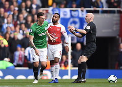 Brighton & Hove Albion's Lewis Dunk and Arsenal's Alexandre Lacazette square up as referee Stuart Taylor looks on