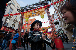 © licensed to London News Pictures. London, UK 22/01/12. A child plays with his dragon toy as people fill Chinatown in London for shopping and sharing the excitement of Chinese New Year on the day before Chinese New Year's Eve. Photo credit: Tolga Akmen/LNP