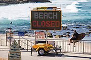 Bronte Beach closed in Sydney due to the Coronavirus Pandemic, Sydney, Australia. Surfers ignore beach closed signage  and climb over to go surfing.
