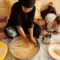 Siham Khaled Mustafa makes hand rolled couscous called maftoul as her grandson watches in the West Bank village of Dayr Balut.