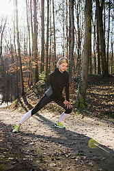 Fit woman stretching on fitness trail