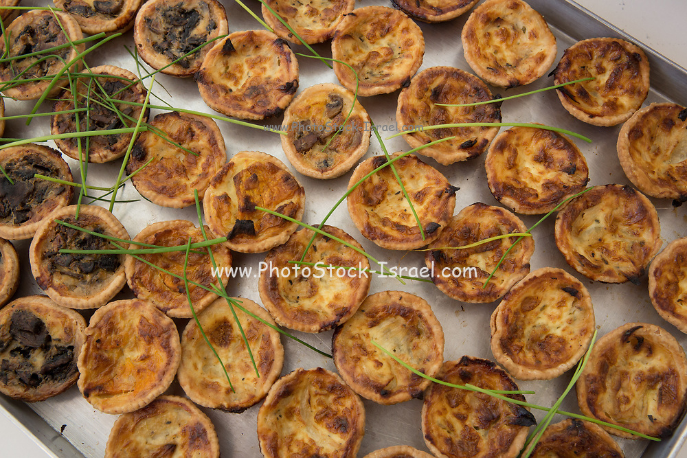A buffet table laden with food. A plate of savoury tartelettes (small tarts with various savoury fillings)