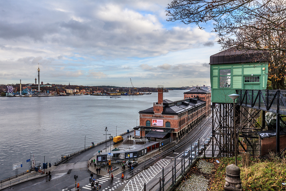 Fotografiska (The Swedish Museum of Photography) in Stockholm, Sweden. It is a center for contemporary photography. Fotografiska houses a gallery, museum shop, academy, cafe, bar, conference rooms, museum shop, gallery, and event spaces. Green building on the left is an old Sofia lift.