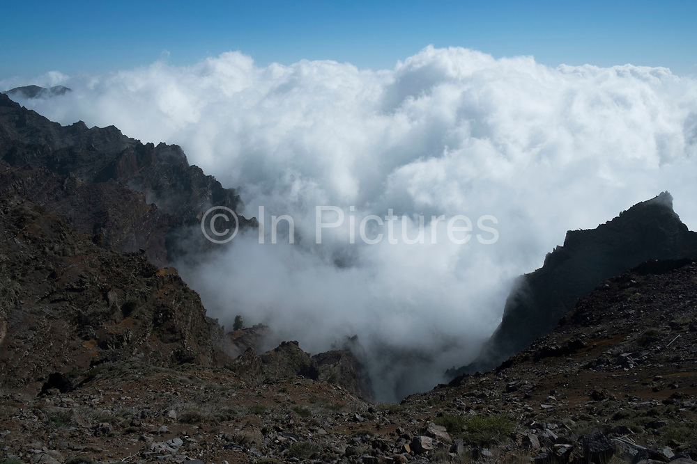 View above the clouds looking south to the Caldera de Taburiente National Park in La Palma, Canary Islands, Spain. La Palma, also San Miguel de La Palma, is the most north-westerly Canary Island in Spain. La Palma has an area of 706 km2 making it the fifth largest of the seven main Canary Islands. Caldera de Taburiente National Park Spanish: Parque Nacional de la Caldera de Taburiente is a national park on the island of La Palma, Canary Islands, Spain. It contains the enormous expanse of the Caldera de Taburiente, once believed to be a huge crater, but nowadays known to be a mountain arch with a curious crater shape, which dominates the northern part of the island. It was designated as a national park in 1954. The caldera is about 10 km across, and in places the walls tower 2000 m over the caldera floor.