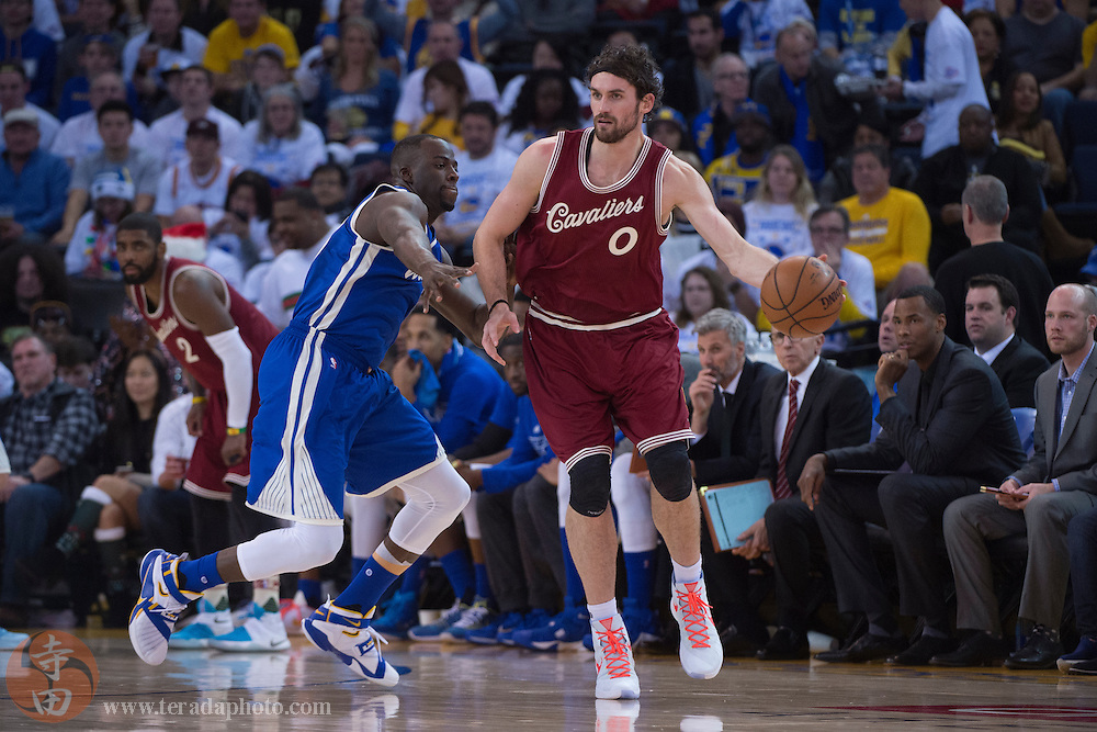 December 25, 2015; Oakland, CA, USA; Cleveland Cavaliers forward Kevin Love (0) dribbles the basketball against Golden State Warriors forward Draymond Green (23) during the third quarter in a NBA basketball game on Christmas at Oracle Arena. The Warriors defeated the Cavaliers 89-83.