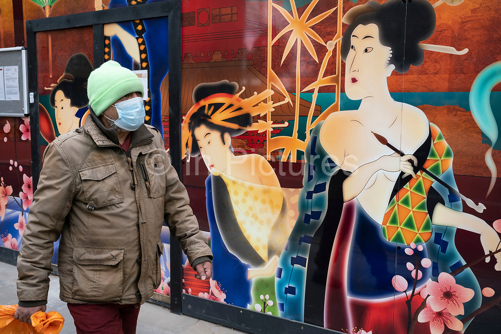 Man wearinga  face mask interacts with a colourful large scale Japanese design illustration on a hoarding outside a shop being refitted in the upmarket area of Chelsea on 14th April 2021 in London, United Kingdom. Chelsea is one of the principal areas for mid-range, exclusive or luxury goods in West London. It is known as a district where the rich and wealthy shop, mostly for high end ad well as high street fashion and jewellery.