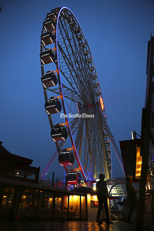It's the calm before the storm at the Seattle Great Wheel, which saw a steady trickle of visitors under drizzly skies on Seattle's waterfront. (Ken Lambert / The Seattle Times)