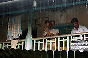 Locals shelter on a balcony as rain cascades from the corrugated iron roof during the monsoon, Goa, India