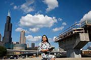 Portrait of UIC College of Engineering alumnus Diana Briones in front of the Chicago skyline and the Jane Byrne Interchange in Chicago,. Briones graduated from UIC with a Bachelor of Science in Civil Engineering in 2017, and now works at TranSmart/EJM, where she helped analyze the traffic detour routes due to the construction of the Interchange.