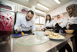25 February 2020, Jerusalem: Teacher Ameer Babeesh shows his catering students how to present a dish. The Lutheran World Federation's vocational training centre in Beit Hanina offers vocational training for Palestinian youth across a range of different professions, providing them with the tools needed to improve their chances of finding work.
