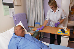 Housekeeper cleaning and chatting to patient on Haematology Ward,