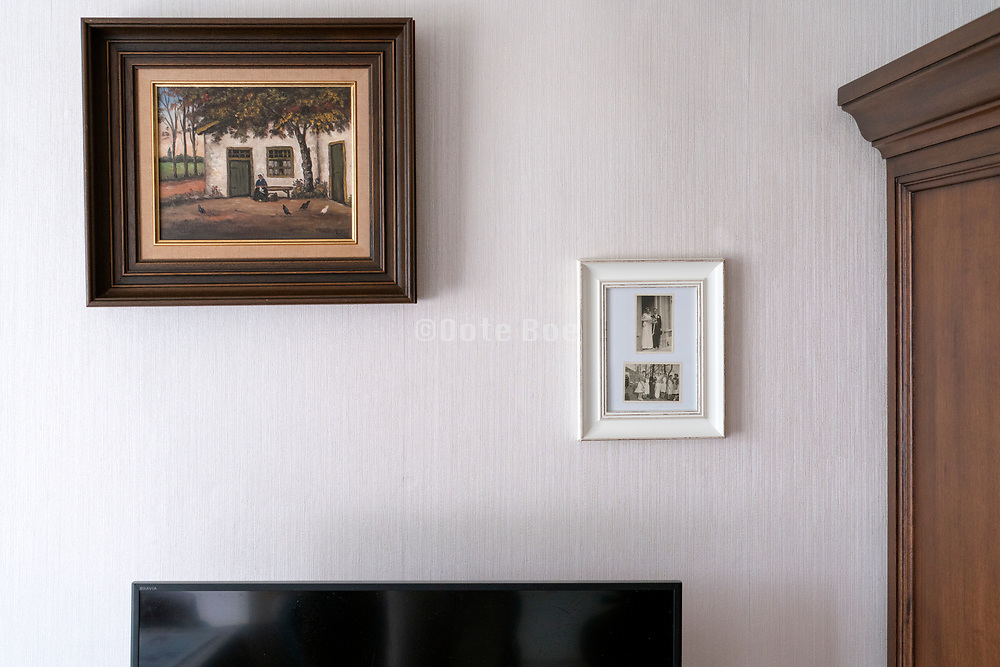 wall with framed family picture and old painting in a retirement house home