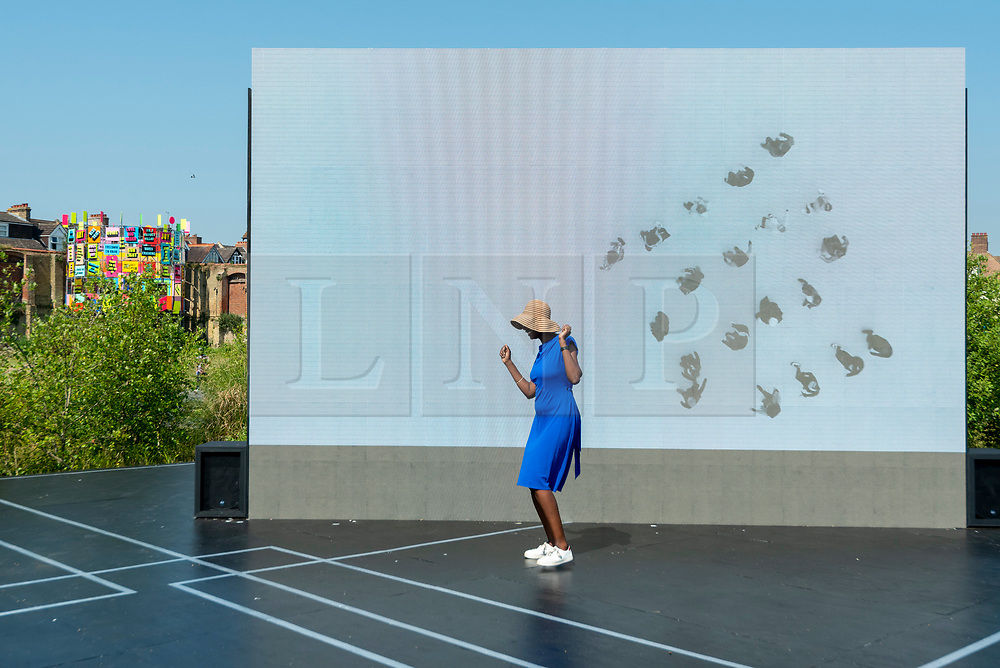 """© Licensed to London News Pictures. 20/07/2021. FOLKESTONE, UK. A woman experiences """"Beautiful Sunday"""", 2021, by Jacqueline Donachie, which celebrates 'all the dance floors of Folkestone' by marking out their size one-to-one on a huge stage set in the middle of the derelict gasworks site. Preview of The Plot exhibition, the fifth Creative Folkestone Triennial. Folkestone has no publicly subsidised art gallery, so artists were invited to use public spaces to create new artworks in the seaside town. Over 20 works by artists including Assemble, Rana Begum, Gilbert & George, Atta Kwami, Pilar Quinteros, and Richard Deacon are on display 22 July to 2 November 2021.  Photo credit: Stephen Chung/LNP"""