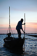 A sand diver prepares his boat early in the morning at Segou, Mali. People dive to the bottom of the Niger River, filling buckets with sand to be used in construction all over the country. Many people die each year doing this dangerous job