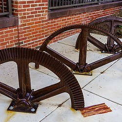 Lititz, PA, USA - August 21, 2020: Large gears from candy making machines are now incorporated into the sidewalk at the former Wilbur Chocolate factory in the downtown area.