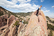 Shawn Olson enjoys the view from the top of a red rock spire in Settlers' Park, Boulder, Colorado.