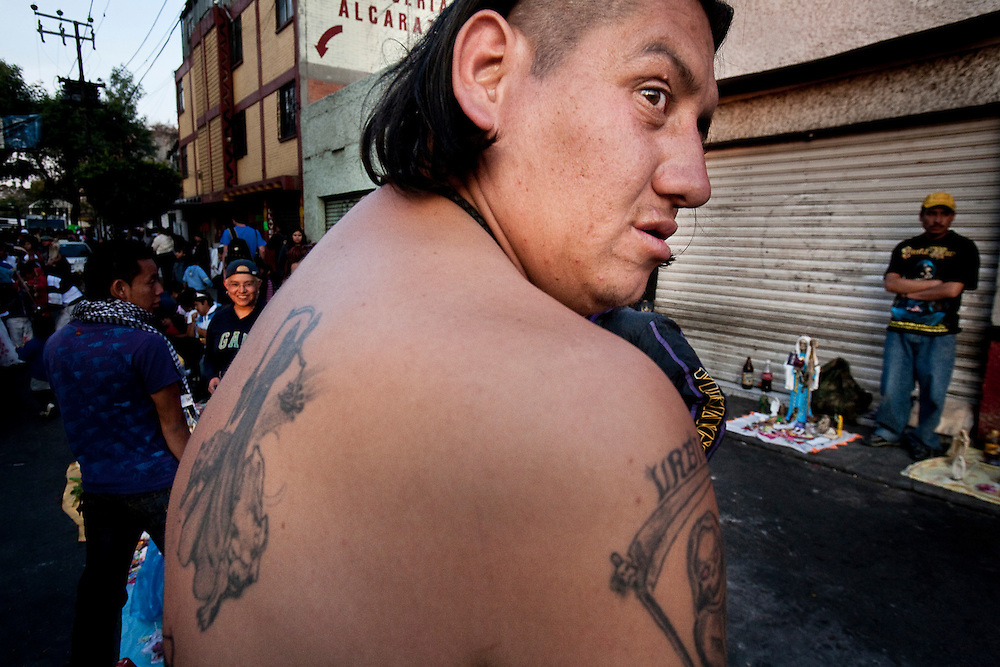 A Sante Muerte devotee worships in front of a popular shrine in Tipito in Mexico City with his shirt off to show tattoos he has gotten that depict Sante Muerte.