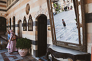 A man and woman glare at a little boy who, reflected in the mirror, uncooperatively stands and cries rather than follow them into the door at Azem Palace.<br /><br />(June 16, 2010)