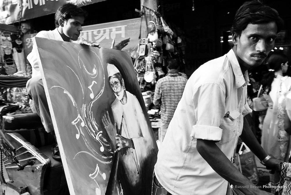 A rickshaw rider looks at the camera while his passenger holds on to a painting in Varanasi, Uttar Pradesh, India