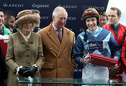 The Prince of Wales and the Duchess of Cornwall with jockey Tom Chatfield-Roberts (right) who won the Prince's Countryside Fund Charity race riding Golden Wedding at Ascot Racourse.