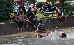 May 29, 2017 - Lahore, Punjab, Pakistan - Pakistani people taking bath in the canal water to beat the heat and get some relief from the extremely hot weather during first day of the holy month of Ramzan ul Mubarak in Lahore. Maximum temperature of 47 degrees Celsius in Lahore was recorded. Experts have forecast the prevailing harsh weather conditions to persist during the next week, sizzling heat forced the people to stay indoors, decreasing traffic on otherwise busy roads at noon and in the afternoon. Lahore canal, as usual, attracted a large number of people including women and children. (Credit Image: © Rana Sajid Hussain/Pacific Press via ZUMA Wire)