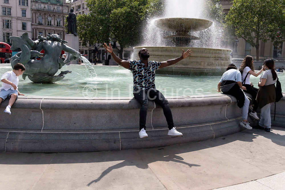 A man expresses joy at the fountains in Trafalgar Square on Covid Freedom Day. This date is what Prime Minister Boris Johnsons UK government has set as the end of strict Covid pandemic social distancing conditions with the end of mandatory face coverings in shops and public transport, on 19th July 2021, in London, England.