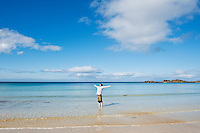 Person stands in Cold water on scenic beach, Gimsøya, Lofoten islands, Norway