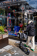A man walks past a Covent Garden retailer while balancing shopping bags on his eScooter, on 24th May 2021, in London, England.
