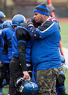 Newburgh, New York - A Middletown coach consoles a player after the Middies lost to Goshen in the Orange County Youth Football League Division II Super Bowl at Newburgh Free Academy on  Nov. 22, 2014.