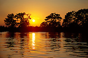 Sunset on Waccamaw River with calm water and cypress trees