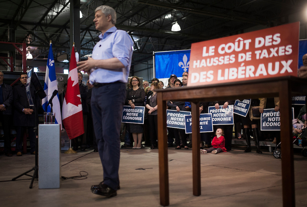 A young girl in the audience looks up as Canada's Prime Minister and Conservative leader Stephen Harper speaks during a campaign rally in Quebec City, October 16, 2015.  Canadians will go to the polls for a federal election on October 19.   REUTERS/Mark Blinch