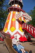 Parents and children playing on a Helter Skelter in Hyde Park, London. This old fashioned fair ground ride is of a classic design and is painted brightly and traditionally in colourful red yellow and white.